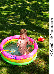 paddling pool child - paddling pool in garden with small boy...