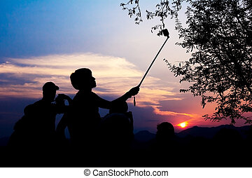 Silhouette of travelers enjoy their moment watching sunset...