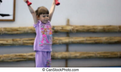 Little girl is engaged in gymnastics with dumbbells