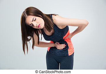 Fitness woman having pain in stomach over gray background