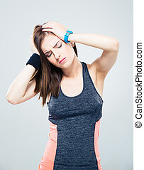 Sports woman having headache over gray background