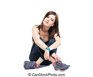 Serious fitness woman resting on the floor isolated on a...