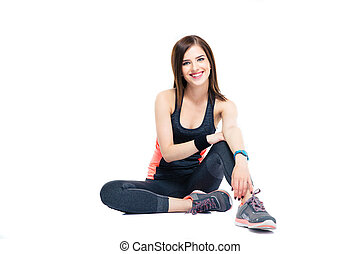 happy sports woman sitting on the floor isolated on a white...