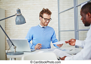 Reading resume - Young manager reading resume of man hiring...