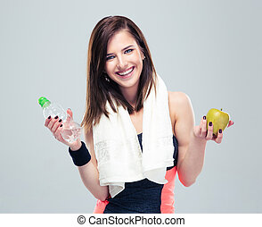 Smiling woman holding apple and bottle with water - Smiling...