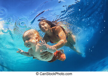 Mother with child swimming underwater in the pool - In blue...