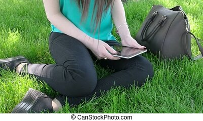 Female student with tablet PC sitting on grass in campus...