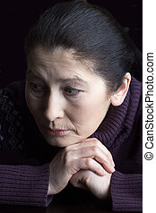 Sad elderly woman - Mature woman in deep sitting thought at...