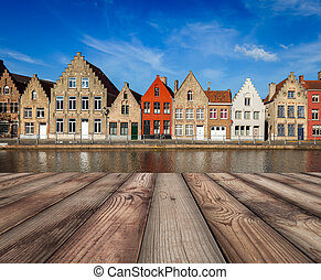 Wooden planks table with European town in background -...