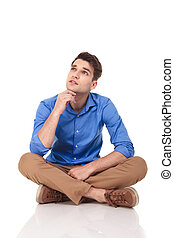 Young fashion man sitting with his legs crossed while...