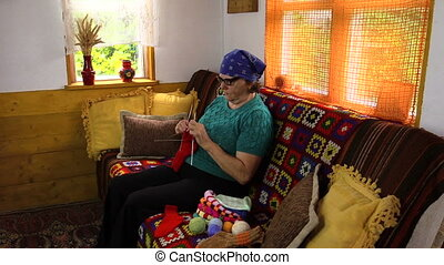 senior woman knit - Old senior grandmother woman sit on sofa...