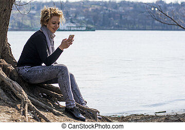 happy young curly blond woman sitting by the river and...