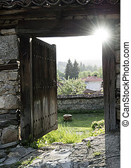 Opened old wood door with panorama and sun rays