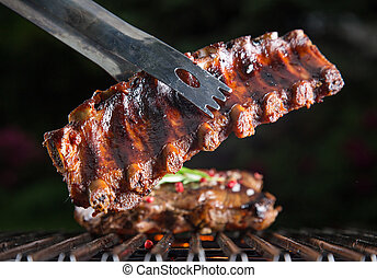 Delicious pork spareribs on grill grate, garden barbecue.