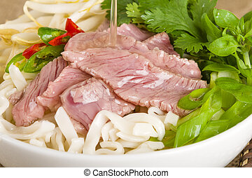 Pho Bo - Vietnamese fresh rice noodle soup with beef, herbs...