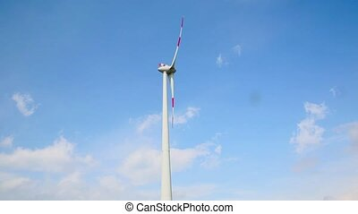 Wind turbine against blue sky and white clouds, power and...