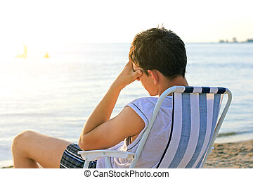 Sad Man at Seaside - Sad Young Man sit on the Beach Chair at...