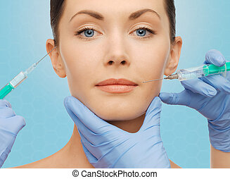 woman face and surgeon hands with syringes - plastic...