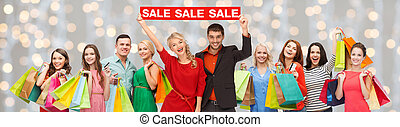 happy people with red sale sign and shopping bags -...