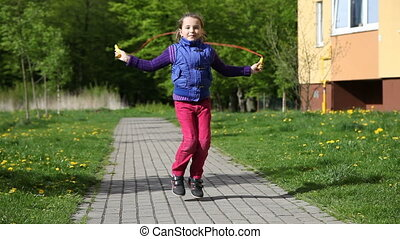 girl jumping rope - girl in a blue jacket and red trousers...