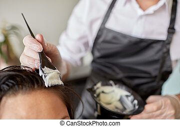 close up of stylist coloring hair at salon - beauty and...