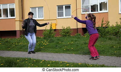 mom with her daughter jumping ropes - mother in a black...