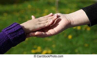 mom's hand gently stroking her daughter's hand a sunny...