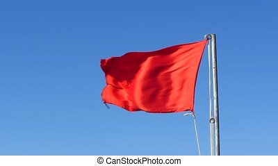 Red flag flies against the blue sky