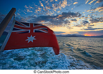 Australian Flag at sunrise over mountains from boat in...