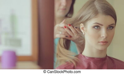 Hairdresser makes hairstyle of model with long hair