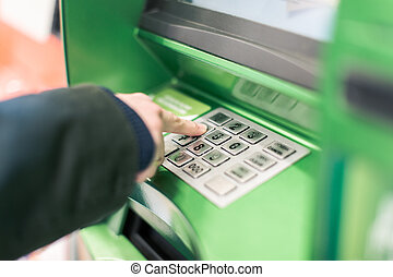 Close-up of hand entering PIN, pass code on ATM