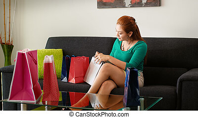 Latina Girl Peeps Into Shopping Bags On Sofa At Home - Young...