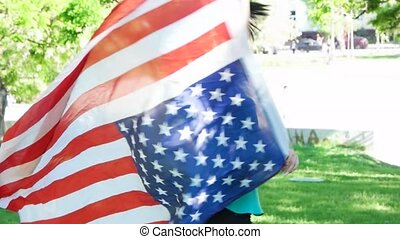Happy patriotic  young woman with the American flag held in her hands dancing slowmo