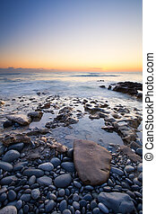 Early morning landscape of ocean over rocky shore and glowing sunrise