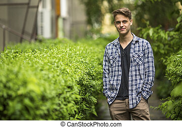 Young guy with his hands in his pockets, in the open air