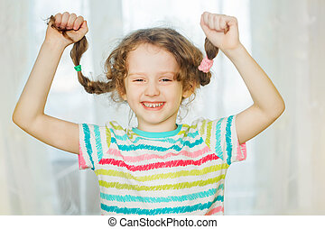 Laughing girl pull her pigtails up by hand and show her...