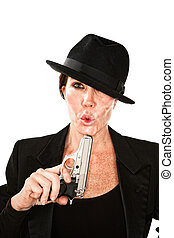 Woman blowing on the end of a smoking gun - Woman blowing on...
