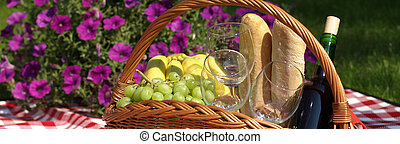 Summer picnic basket with fruits, glasses and bottle of wine