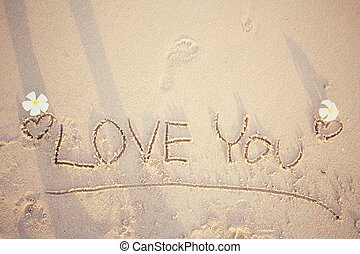 The word love you written in sand on beach