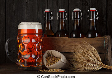 Beer glass on table with crate full of bottles, with brewing...