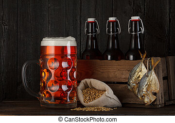 Glass of beer on table with wooden crate full of bottles,...
