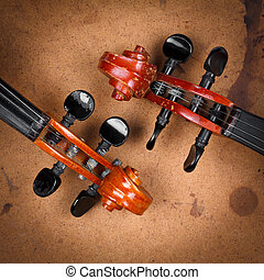 Old violin scrolls detail over grunge background
