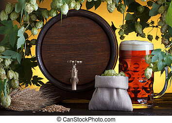 Vintage beer barrel with beer glass and fresh hops, with...