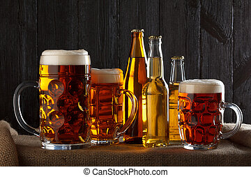 Assortment of beer glasses on table with burlap cloth, dark...