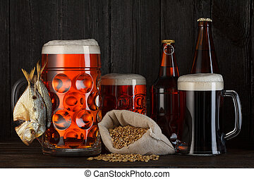 Beer mugs and bottles assortment with smoked salty fish,...