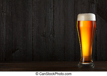 Glass of beer on wooden table, dark background with copy...