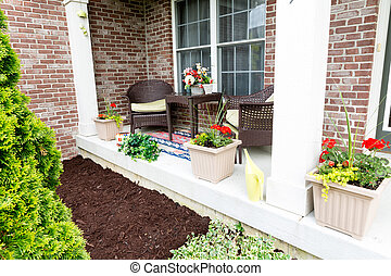 Mulching flowerbeds around the house with a freshly mulched...