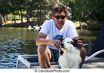 Man with contented dog on dock - Dog enjoying attention from...