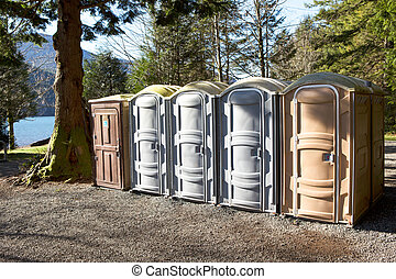 Portapotty in a park yard for public convenience -...