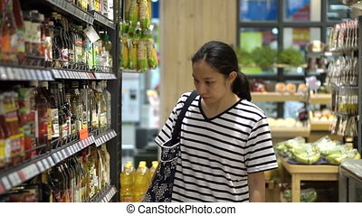 Asian girl shopping in supermarket - Chiangmai, Thailand -...